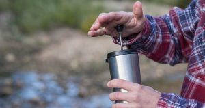 Pushing the plunger down on a French Press travel mug while camping by a river.