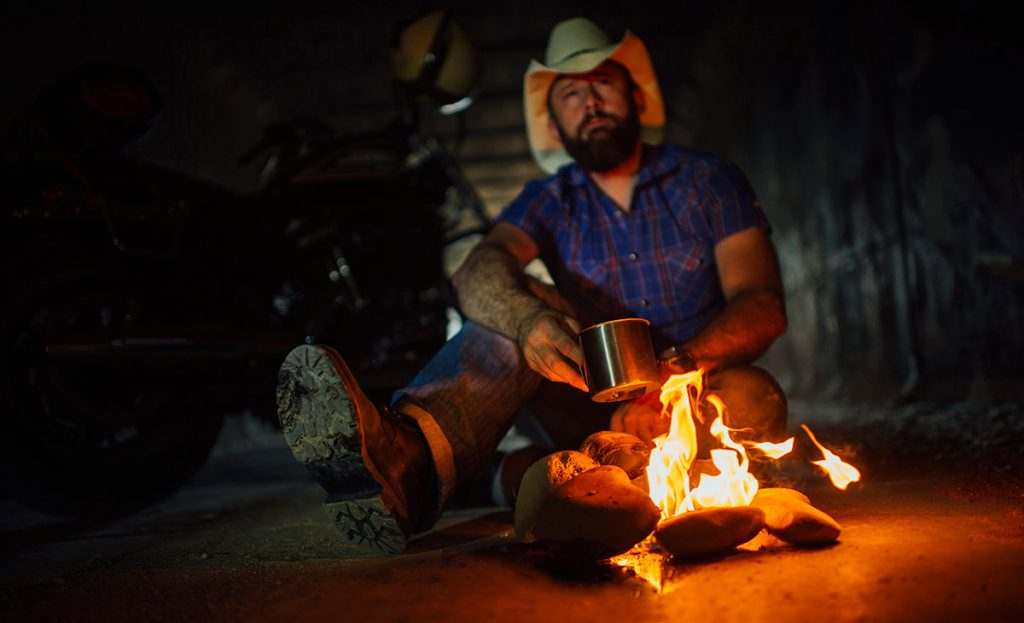 A man in a cowboy hat sitting next to a camp fire drinking cowboy coffee.